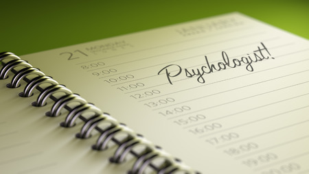 important date: Closeup of a personal calendar setting an important date representing a time schedule. The words Psychologist written on a white notebook to remind you an important appointment. Stock Photo