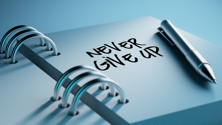 up to date: Closeup of a personal agenda setting an important date writing with pen. The words Never give up written on a white notebook to remind you an important appointment.