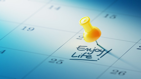 yellow push pin: Concept image of a Calendar with a yellow push pin. Closeup shot of a thumbtack attached. The words Enjoy Life written on a white notebook to remind you an important appointment. Stock Photo