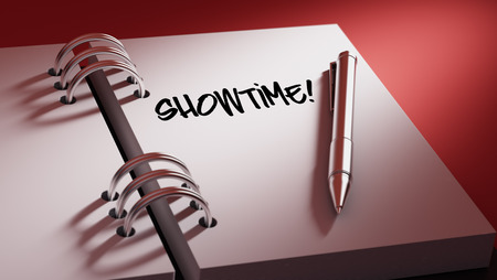 showtime: Closeup of a personal agenda setting an important date writing with pen. The words Showtime written on a white notebook to remind you an important appointment.