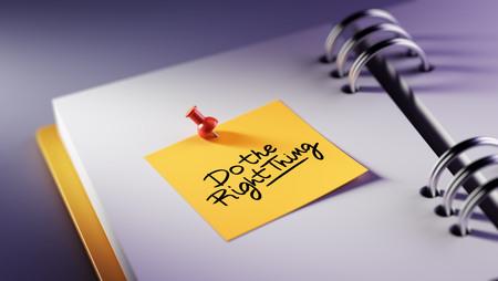 Close-up Yellow Sticky Note Plak het in een notitieboek met een afspraak. De woorden Doe het juiste wat op een wit notitieboekje om u een belangrijke afspraak te herinneren.