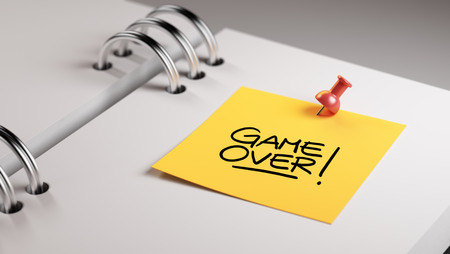 the game is over: Closeup Yellow Sticky Note paste it in a notebook setting an appointment. The words Game over written on a white notebook to remind you an important appointment.