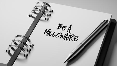 millonario: Primer plano de una fijación de una fecha importante escribir con la pluma agenda personal. Las palabras ser millonario por escrito en un cuaderno en blanco para que le recuerde una cita importante.