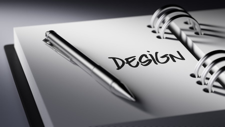 agenda: Closeup of a personal agenda setting an important date writing with pen. The words Design written on a white notebook to remind you an important appointment. Stock Photo
