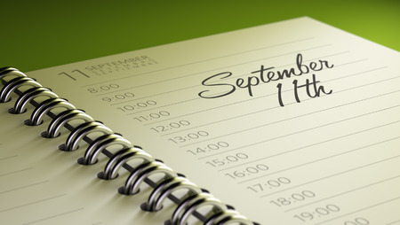 11th: Closeup of a personal calendar setting an important date representing a time schedule. The words September 11th written on a white notebook to remind you an important appointment. Stock Photo