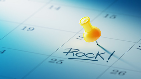 yellow push pin: Concept image of a Calendar with a yellow push pin. Closeup shot of a thumbtack attached. The words Rock written on a white notebook to remind you an important appointment. Stock Photo