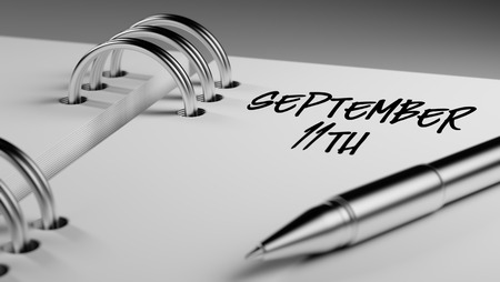 11th: Closeup of a personal agenda setting an important date writing with pen. The words September 11th written on a white notebook to remind you an important appointment.