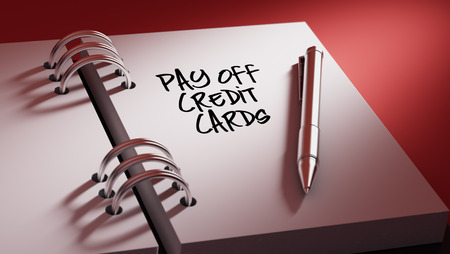 pay off: Closeup of a personal agenda setting an important date writing with pen. The words Pay off Credit cards written on a white notebook to remind you an important appointment.