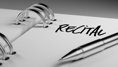 recital: Closeup of a personal agenda setting an important date writing with pen. The words Recital written on a white notebook to remind you an important appointment. Stock Photo