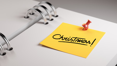 christmas paste: Closeup Yellow Sticky Note paste it in a notebook setting an appointment. The words Christmas written on a white notebook to remind you an important appointment.