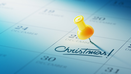 yellow push pin: Concept image of a Calendar with a yellow push pin. Closeup shot of a thumbtack attached. The words Christmas written on a white notebook to remind you an important appointment. Stock Photo