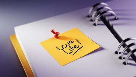 love life: Closeup Yellow Sticky Note paste it in a notebook setting an appointment. The words Love life written on a white notebook to remind you an important appointment.