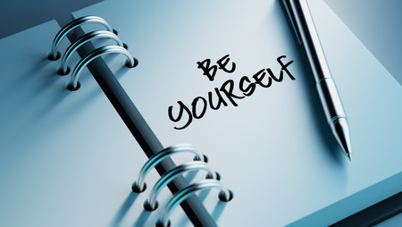 be yourself: Closeup of a personal agenda setting an important date writing with pen. The words be yourself written on a white notebook to remind you an important appointment. Stock Photo