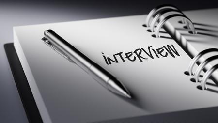 comunicacion oral: Primer plano de una fijaci�n de una fecha importante escribir con la pluma agenda personal. La Entrevista palabras escritas en un cuaderno en blanco para que le recuerde una cita importante.