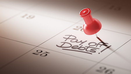 pay off: Concept image of a Calendar with a red push pin. Closeup shot of a thumbtack attached. The words Pay off debts written on a white notebook to remind you an important appointment. Stock Photo
