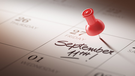 11th: Concept image of a Calendar with a red push pin. Closeup shot of a thumbtack attached. The words September 11th written on a white notebook to remind you an important appointment.