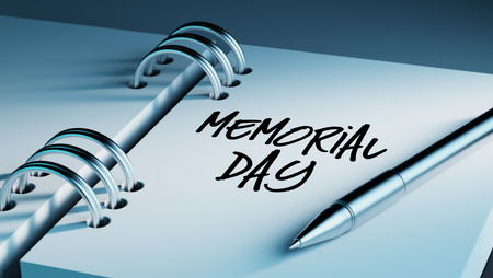 important date: Closeup of a personal agenda setting an important date writing with pen. The words Memorial Day written on a white notebook to remind you an important appointment. Stock Photo