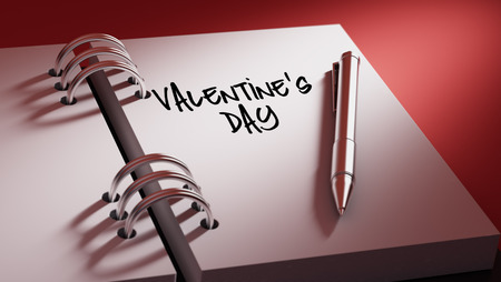 important date: Closeup of a personal agenda setting an important date writing with pen. The words Valentines Day written on a white notebook to remind you an important appointment.