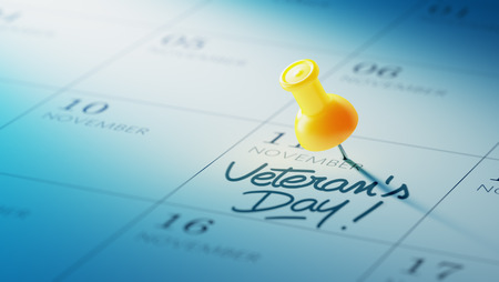 yellow push pin: Concept image of a Calendar with a yellow push pin. Closeup shot of a thumbtack attached. The words Veterans Day written on a white notebook to remind you an important appointment. Stock Photo