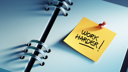 harder: Closeup Yellow Sticky Note paste it in a notebook setting an appointment. The words Work Harder written on a white notebook to remind you an important appointment.