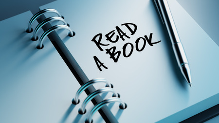 date book: Closeup of a personal agenda setting an important date writing with pen. The words Read a book written on a white notebook to remind you an important appointment. Stock Photo