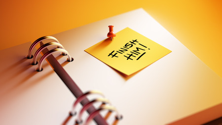 liquidate: Closeup Yellow Sticky Note paste it in a notebook setting an appointment. The words Finish Him written on a white notebook to remind you an important appointment. Stock Photo