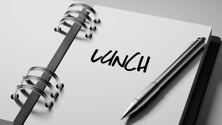 Closeup of a personal agenda setting an important date writing with pen. The words Lunch written on a white notebook to remind you an important appointment.