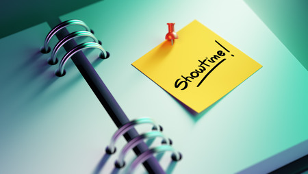 showtime: Closeup Yellow Sticky Note paste it in a notebook setting an appointment. The words Showtime written on a white notebook to remind you an important appointment. Stock Photo