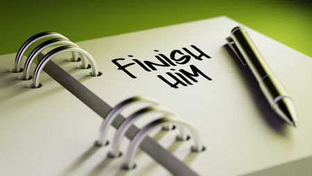 liquidate: Closeup of a personal agenda setting an important date writing with pen. The words Finish Him written on a white notebook to remind you an important appointment. Stock Photo