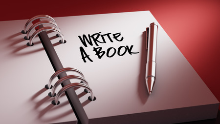 appointment book: Closeup of a personal agenda setting an important date writing with pen. The words Write a Book written on a white notebook to remind you an important appointment. Stock Photo