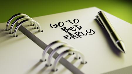 cansancio: Primer plano de una fijaci�n de una fecha importante escribir con la pluma agenda personal. Las palabras Ir a la cama temprano por escrito en un cuaderno en blanco para que le recuerde una cita importante. Foto de archivo