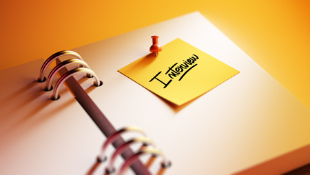 oral communication: Closeup Yellow Sticky Note paste it in a notebook setting an appointment. The words Interview written on a white notebook to remind you an important appointment. Stock Photo
