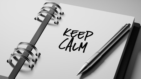 important date: Closeup of a personal agenda setting an important date writing with pen. The words Keep Calm written on a white notebook to remind you an important appointment.
