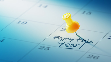 yellow push pin: Concept image of a Calendar with a yellow push pin. Closeup shot of a thumbtack attached. The words Enjoy this year written on a white notebook to remind you an important appointment. Stock Photo