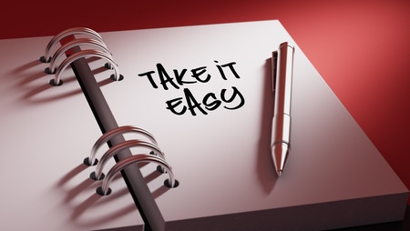 take it easy: Closeup of a personal agenda setting an important date writing with pen. The words Take it easy written on a white notebook to remind you an important appointment.