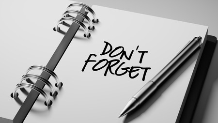 don't: Closeup of a personal agenda setting an important date writing with pen. The words Don`t Forget written on a white notebook to remind you an important appointment.