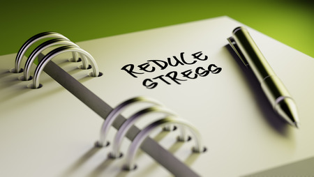 elimination: Closeup of a personal agenda setting an important date writing with pen. The words Reduce Stress written on a white notebook to remind you an important appointment.