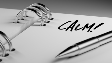 reflexive: Closeup of a personal agenda setting an important date writing with pen. The words Calm written on a white notebook to remind you an important appointment. Stock Photo
