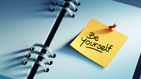 be yourself: Closeup Yellow Sticky Note paste it in a notebook setting an appointment. The words be yourself written on a white notebook to remind you an important appointment.