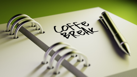 important date: Closeup of a personal agenda setting an important date writing with pen. The words Coffee Break written on a white notebook to remind you an important appointment. Stock Photo