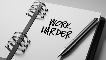 harder: Closeup of a personal agenda setting an important date writing with pen. The words Work Harder written on a white notebook to remind you an important appointment.