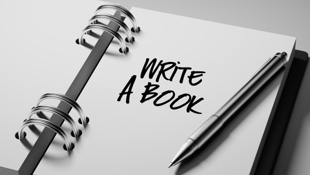 date book: Closeup of a personal agenda setting an important date writing with pen. The words Write a Book written on a white notebook to remind you an important appointment. Stock Photo