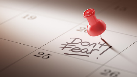 dont: Concept image of a Calendar with a red push pin. Closeup shot of a thumbtack attached. The words Dont Fear written on a white notebook to remind you an important appointment.