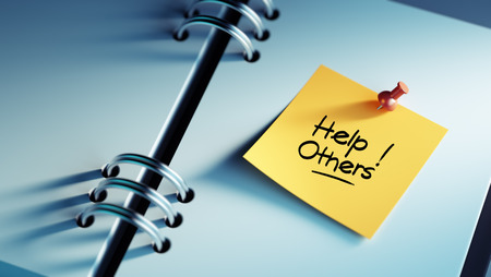 helping others: Closeup Yellow Sticky Note paste it in a notebook setting an appointment. The words Help Others written on a white notebook to remind you an important appointment. Stock Photo