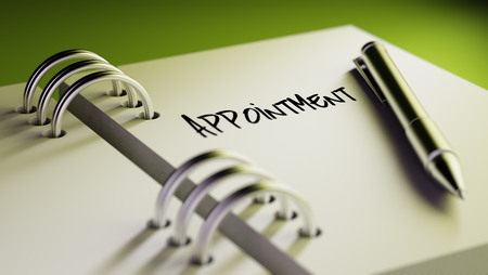 important date: Closeup of a personal agenda setting an important date writing with pen. The words Appointment written on a white notebook to remind you an important appointment. Stock Photo