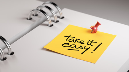 take it easy: Closeup Yellow Sticky Note paste it in a notebook setting an appointment. The words Take it easy written on a white notebook to remind you an important appointment.