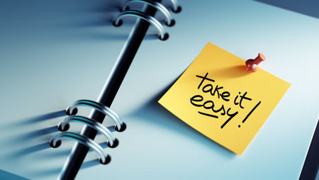 take a note: Closeup Yellow Sticky Note paste it in a notebook setting an appointment. The words Take it easy written on a white notebook to remind you an important appointment.