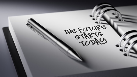 black empowerment: Closeup of a personal agenda setting an important date writing with pen. The words The future starts today written on a white notebook to remind you an important appointment. Stock Photo