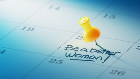 yellow push pin: Concept image of a Calendar with a yellow push pin. Closeup shot of a thumbtack attached. The words Be a better woman written on a white notebook to remind you an important appointment.