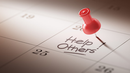 helping others: Concept image of a Calendar with a red push pin. Closeup shot of a thumbtack attached. The words Help Others written on a white notebook to remind you an important appointment.